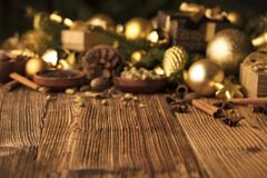 Christmas theme. Christmas decoration in golden and brownish aesthetics with presents in boxes, golden baubles, christmas spices all on a rustic wooden Stock Image