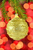 Christmas decoration, golden Christmas ball hanging on spruce twig Stock Photo