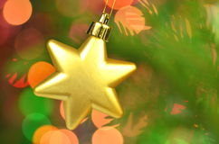 Christmas decoration, golden Christmas star ball hanging on spruce twig Stock Photo