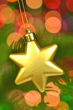 Christmas decoration, golden Christmas star ball hanging on spruce twig Royalty Free Stock Images
