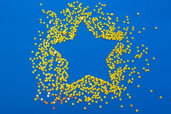 Christmas decoration of golden confetti stars against blue backg Stock Photos
