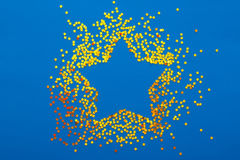 Christmas decoration of golden confetti stars on blue background Royalty Free Stock Images