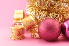 Christmas decoration golden and pink. Conceptual image about Christmas. Christmas decoration with golden drums, gifts, garlands and purples baubles Stock Photos