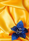 Christmas decoration on golden sateen. With blue flower royalty free stock photos