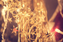 Christmas decoration with golden stars on christmas garland in warm lights Stock Image