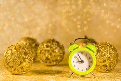 Christmas decoration. Green alarm clock in front of golden Christmas decorations Stock Photos