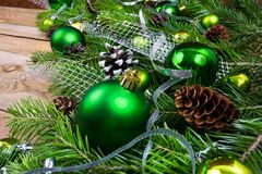 Christmas decoration with green balls, fir cones and silver ribbon royalty free stock photography