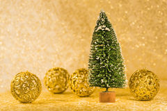Christmas decoration. Green fir covered with snow and golden Christmas decorations Stock Image