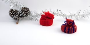 Christmas decoration handmade red hats. Christmas decoration red hats and pine cones. Silver ribbon, soft white background Stock Photography
