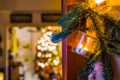 Christmas decoration hanging from door. Christmas decorationmade with a glass vase and a candle inside with some christmas tree 's branch hanging from door with Stock Photography