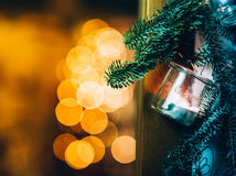 Christmas decoration hanging from door. Christmas decorationmade with a glass vase and a candle inside with some christmas tree 's branch hanging from door with Royalty Free Stock Images
