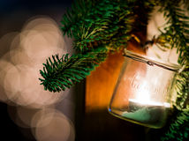 Christmas decoration hanging from door. Christmas decorationmade with a glass vase and a candle inside with some christmas tree 's branch hanging from door with Stock Photo
