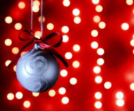 Christmas decoration hanging from a string in front of festive lights blurred out to create bokeh Royalty Free Stock Image