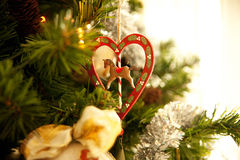 Christmas decoration with heart and horse. Christmas decoration of wood in the shape of a heart with a horse hanging from a tree Stock Photography
