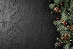Christmas decoration on holiday background with Fir branches, pine cones, red decoration. Xmas and Happy New Year theme. Flat lay, top view, space for text royalty free stock image