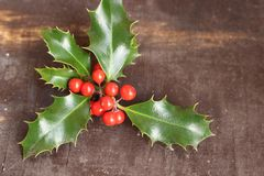 Christmas decoration with holly leaves and berries, isolated on a wooden background. stock photo