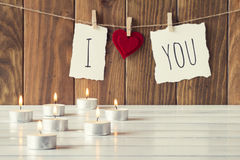 Christmas decoration. I love you is hanging on a rope with clothespins. Some candles on a white wooden table. A brown wainscot as background. Vintage Style Royalty Free Stock Photography