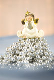 Christmas Decoration Little Angel. Christmas decoration angel sitting on silver beads Royalty Free Stock Photo