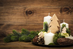 Christmas decoration  made from candles and floristic accesories on the wooden background. Christmas decoration  made from candles and floristic accesories on Stock Image