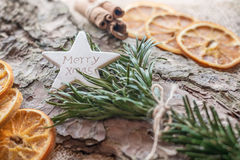 Christmas decoration. With a merry Christmas greeting on star in pine branch on bark Stock Image