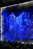 Christmas decoration. Night window on Fifth Avenue. Blue color decorations in the form of a festive table, crystal chandeliers, and a ladys figure standing near Stock Photos