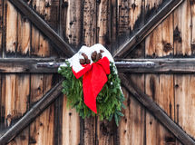 Christmas decoration on old barn. Christmas decoration of red ribbon and evergreen boughs hanging on old weathered barn door and covered with snow in Stock Photography