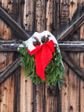 Christmas decoration on old barn. Christmas decoration of red ribbon and evergreen boughs hanging on old weathered barn door and covered with snow in Royalty Free Stock Photography