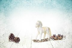 Christmas bauble horse and fir cones on white wooden background stock photography