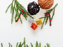 Christmas decoration or ornament laid in frame shape composed of green pine branch, red and green cane, brown and black wooden bal stock photo