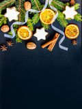 Christmas decoration over dark wood background. Top view of homemade butter nuts star shaped cookies with icing, pine, orange royalty free stock photography