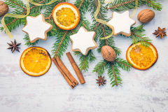Christmas decoration over white wood background. Top view of homemade butter nuts star shaped cookies with icing, pine, orange. Slices,cinnamon, anise, walnuts royalty free stock photos