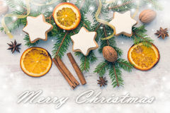 Christmas decoration over white wood wood background. Top view of homemade butter nuts star shaped cookies with icing, pine, orang Royalty Free Stock Images
