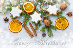 Christmas decoration over white wood wood background. Top view of homemade butter nuts star shaped cookies with icing, pine, orang Stock Images