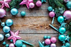 Christmas decoration pattern. Pink and blue stars and balls near pine branches on wooden background top view copyspace Stock Photography