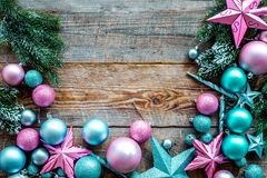 Christmas decoration pattern. Pink and blue stars and balls near pine branches on wooden background top view copyspace Stock Images