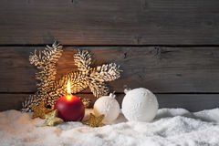 Christmas decoration on pile of snow against wooden wall Stock Images