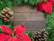 Christmas decoration with pine cones and poinsettia on wooden ba Royalty Free Stock Photo