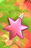 Christmas decoration, pink Christmas star ball hanging on spruce twig Royalty Free Stock Photo