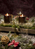 Christmas decoration. Christmas place setting with candles, are wine glasses on the table, pine tree branches are adorned with decorative snow Stock Image