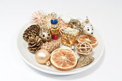Christmas decoration on a plate. Golden decoration on a white plate Royalty Free Stock Photography