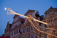 Christmas decoration in Prague. Moon shine and lighting angel with trumpet as decoration on Christmas market in Prague Old Town Square Royalty Free Stock Images