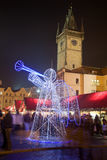 Christmas decoration in Prague. Lighting angel with trumpet as decoration on Christmas market in Prague on Old Town Square with tower of Old Town Hall in the Stock Photos