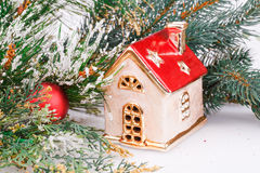 Christmas decoration. With red ball, fir-tree branch and toy house Stock Image