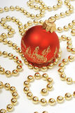 Christmas decoration: red ball and golden beads. On white background Stock Image