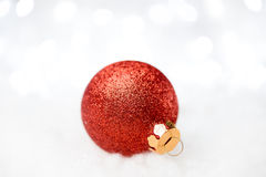 Christmas Decoration with Red Ball in the Snow on the Blurred Background with Holiday Lights. Greeting Card Stock Photography