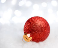 Christmas Decoration with Red Ball in the Snow on the Blurred Background with Holiday Lights. Greeting Card Stock Images