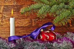 Christmas decoration. Red ball, violet ribbon, fir-tree, candle Stock Images
