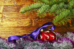 Christmas decoration. Red ball with violet ribbon, fir-tree Royalty Free Stock Photos