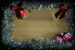 Christmas decoration. Red christmas ball on the wooden background with silver string as a delimitation. Free space for some text or wishes. Merry X-mas Royalty Free Stock Photography