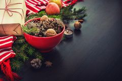 Christmas decoration - red bowl full of fir-cones, gift box wrapped in kraft paper, pine branches, candle, nuts, anise, apples and stock image